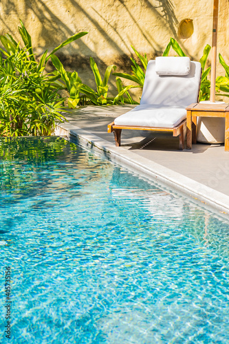 Billede på lærred Umbrella and chair around outdoor swimming pool