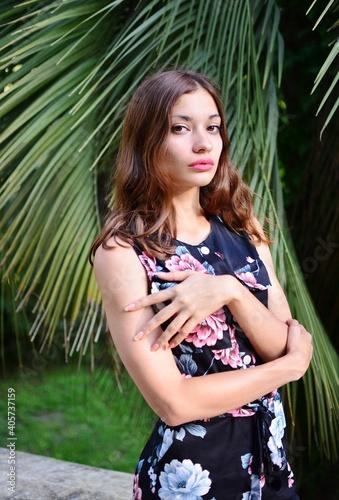Obraz Portrait Of Beautiful Woman Standing Against Plants - fototapety do salonu