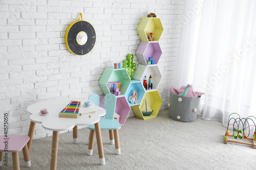 Child room interior with colorful shelves near brick wall