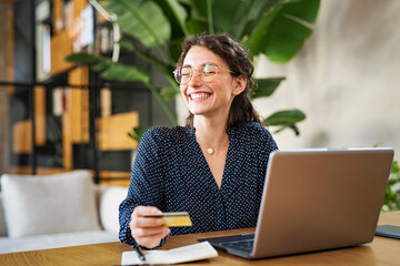 Woman with laptop using credit card