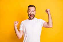Portrait Of Attractive Lucky Cheerful Bearded Guy Celebrating Best Luck Isolated Over Bright Yellow Color Background