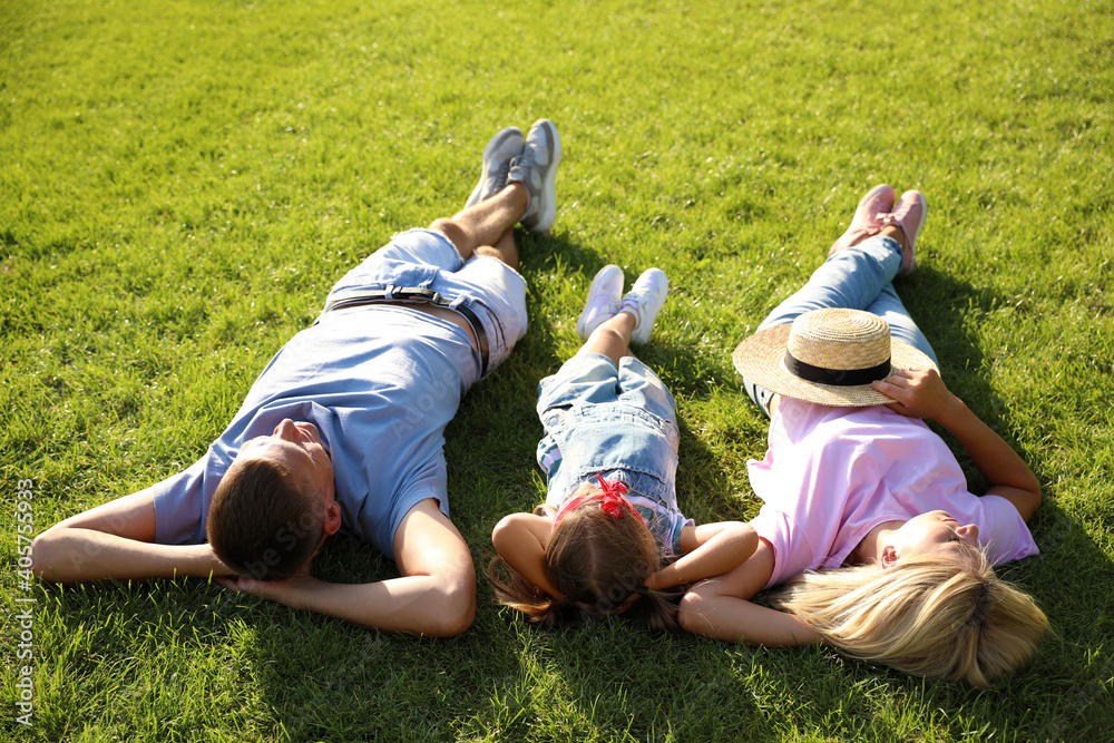Fototapeta Happy parents with their child lying on green grass. Spending time in nature