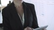 Grey-haired businesswoman in glasses holding tablet and typing. Female CEO standing near screen with presentation. Blurred colleague on background. Vertical motion. Business and management concept
