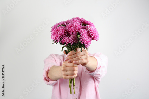 Fotografie, Obraz Woman with bouquet of beautiful asters on light background, closeup