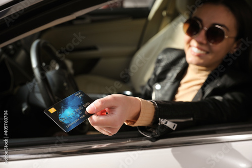 Woman sitting in car and giving credit card at gas station, focus on hand