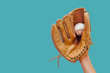 Hand In A Leather Baseball Glove Catches A White Ball In Defocus On A Red Background