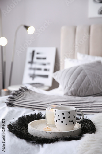 Cup of drink and burning candles on bed in room, space for text. Interior design