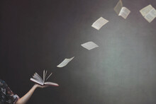 Surreal Moment Of Pages Flying From A Book Held By A Woman