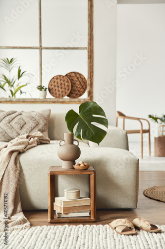 Stylish composition of living room with design beige sofa, wooden stool, tropical leaf in vase, book, decoration, furniture and elegant personal accessories. Modern home decor. Open space. Template.