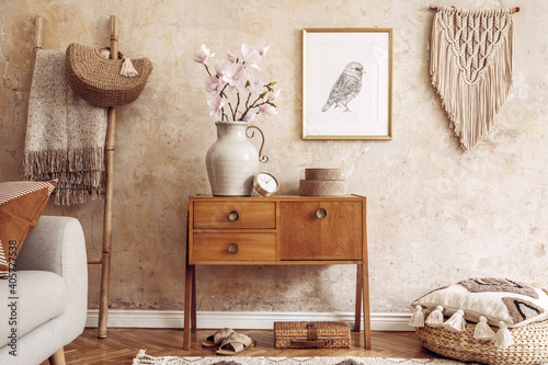 Obraz Modern retro composition of living room with wooden vintage commode, sofa, rattan pouf, ladder, macrame, carpet, pillow, gold mock up poster frame, flowers, decoration and personal accessories. - fototapety do salonu