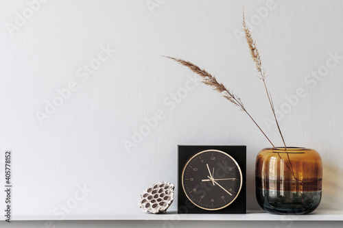 Minimalistic composition on the wooden shelf with dried flowers in vase and elegant personal accessories in stylish living room interior. Copy space.
