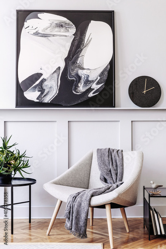 Stylish scandinavian home interior of living room with design gray armchair, modern stool, black coffee table, modern paintings, decoration, plant and elegant personal accessories in home decor.