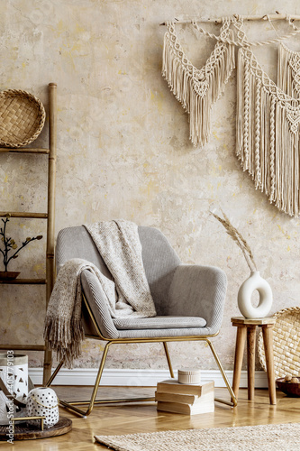 Photo Stylish oriental living room with design armchair, beautiful macrame, wooden ladder, plant, decoration, carpet, coffee table, book and elegant personal accessories in wabi sabi concept
