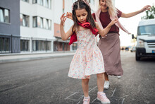 A Happy Little Girl Playing Hopscotch With Her Mother On A Playground Outside. A Child Plays With Her Mom. Kid Plays With Mum Hopscotch Drawn On The Pavement. Activities And Games For Children.