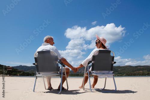 Canvastavla coppia di anziani si tiene teneramente la mano seduti in una sedia in spiaggia