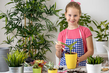 Young Girl Having Fun With Putting Fertile Soil In The Flowerpot With A Plant In It