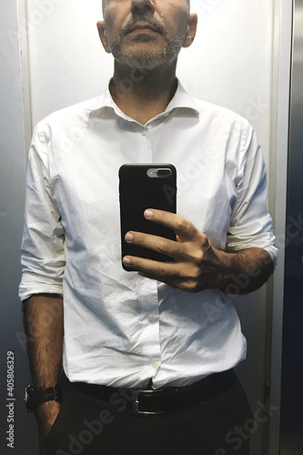 Fototapeta Midsection Of Man Using Mobile Phone While Standing At Home