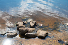 A Pile Of Smooth Stones On The Sandy Bottom Of The River Near The Shore, Background