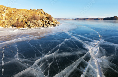 Frozen Baikal Lake on a sunny winter day. Beautiful transparent blue ice with cracks in the Kurkut Bay. Environment and ecology. Winter travel. Natural cold background (focus on ice)