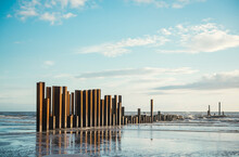 Large Rusty Steel Construction Pillars In The Sand On A Sunny Beach, With Blue Sky And Calm Waves. The Steel Girders Are Rusty. Building And Construction On The Coast. Development And Building