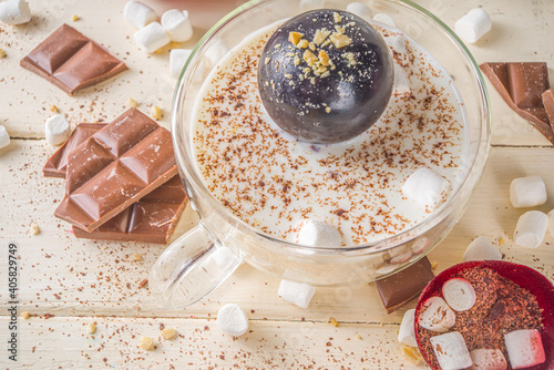 Obraz Hot chocolate bomb, with marshmallow and chocolates and nuts,  Woman's hand dropping chocolate bomb into cup with milk. - fototapety do salonu