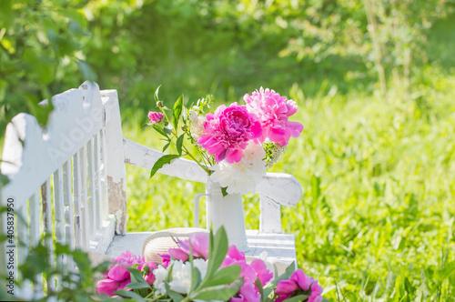 Obraz peony in jug on white wooden bench in summer garden - fototapety do salonu