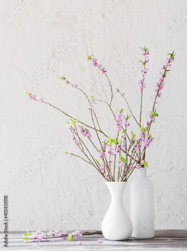 Canvas Print daphne flowers in vase on old wooden table on background white wall