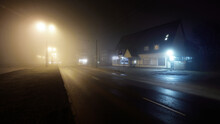 An Empty Illuminated Motorway And Closed Shops In A Fog At Night. Road Sign Close-up. Dark Urban Scene, Cityscape. Riga, Latvia. Dangerous Driving, Concept Image