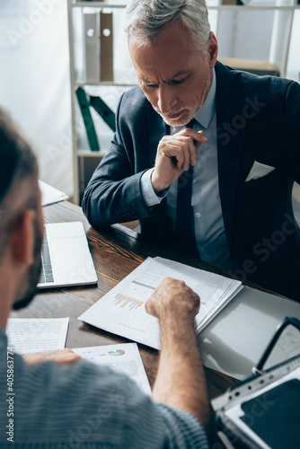 Pensive investor looking at papers with graphs near laptop and businessman on blurred foreground