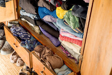 Old Clothes And Shoes In An Overflowing Closet. Second Hand Reuse. Decluttering And Cleaning The Cabinet. Second Hand Reuse. Decluttering And Cleaning The Cabinet