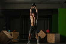 Full-length Photo Of A Handsome Man With A Naked Torso Exercising With A Kettlebell On A Dark Background
