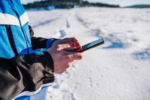 Close Up Of Man Hiking In Snowy Mountain In A Sunny Day Using Mobile Phone. Technology And Nature. Winter Season