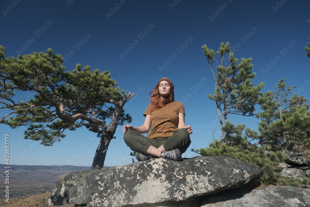 Fototapeta Young Woman Doing Yoga On Rock Against Clear Sky