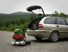 Green Full-packed Backpack (rucksack) Behind A Station Wagon Car With Open Trunk Full Of Camping Equipment Before A Multi-day Hike. Hitchhiking With Tent And Sleeping Mat Through Swedish Lapland.