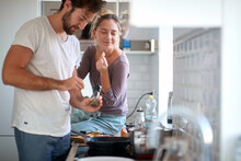 A Young Girl Enjoying In A Meal Preparation By Her Boyfriend. Cooking, Home, Kitchen, Relationship
