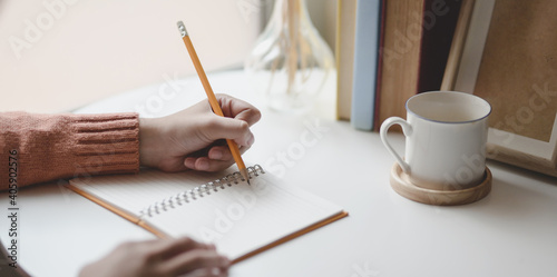 Canvas Print Cropped Image Of Hand Holding Pencil Over Book By Coffee Cup On Table