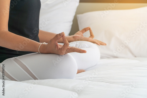 Obraz Midsection Of Woman Meditating On Bed At Home - fototapety do salonu