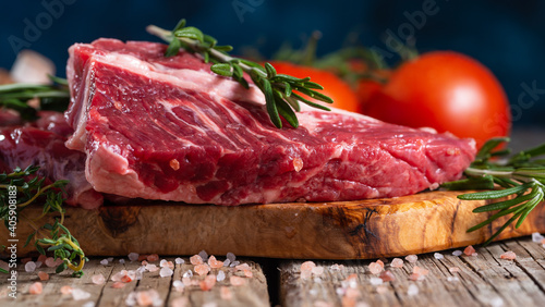 Leinwand Poster Raw pork or beef meat with tomatoes and rosemary on wooden cutting board o blue background