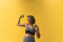 Happy Sportswoman Picking Two Apples On A Yellow Background
