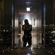 Leinwandbild Motiv Rear View Of Man Standing In Corridor Seen Through Glass Window At Night