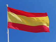 Low Angle View Of Spanish Flag Against Clear Blue Sky