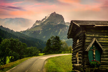 Wooden Alpine Hut With A God Statue And With The Alpine Mountains In The Background At Sunset