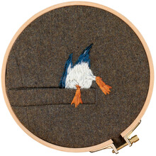 Embroidery Of Bird On The Pocket On A Round Hoop On A White Background