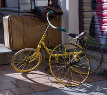 Closeup Shot Of An Old And Rusty Bike Near The Suitcase In The Street
