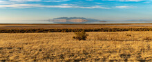 Panoramic View Of Grasslands, A Lake And A Mountain Across The Lake Reflecting On The Water