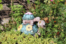 Closeup Of Small Decorative Turtle Sculptures On Plants In A Garden