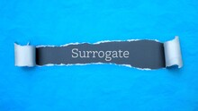 Surrogate. Blue Torn Paper Banner With Text Label. Word In Gray Hole.