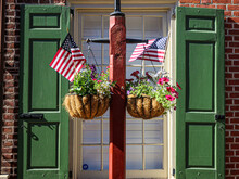 Pole With Flower Baskets And The American Flag Hanging On Window Background