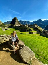 Full Length Of Woman Sitting On Rock At Machu Picchu Against Blue Sky