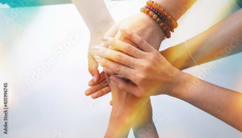 Fotografia Cropped Image Of Female Friends Stacking Hands Over White Table